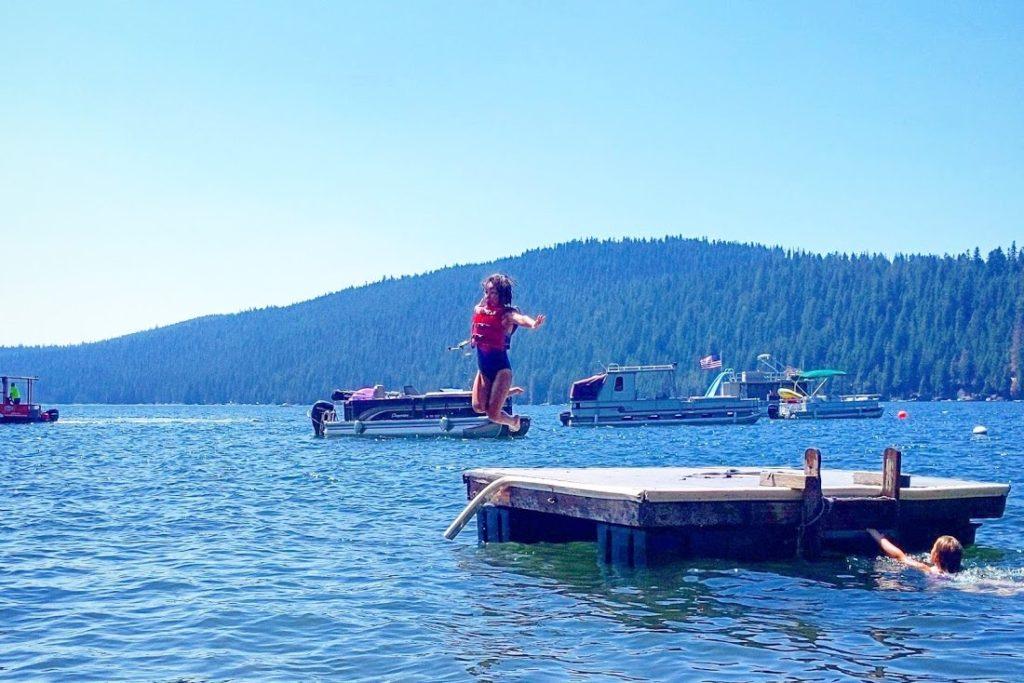 Girl jumping off of a dock at Lake.